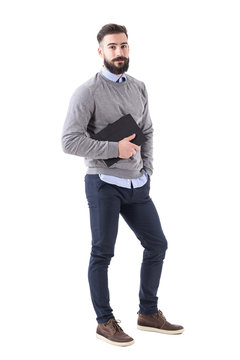 Handsome relaxed stylish bearded teacher with notebook looking at camera. Full body length portrait isolated on white studio background.