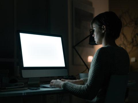 Woman using a computer at night