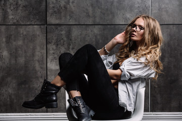 A girl with long blonde hair dressed in black jeans, a striped shirt and black shoes sitting on the bed with blue linens. Fashionable casual outfit.
