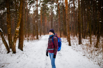Photo of side view of smiling girl in hat with backpack over winter forest