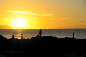 Sunset on shark cove beach and peoples in Hawaii