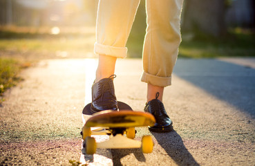 Female riding a skateboard at sunset