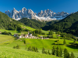 Val di Funes valley, Santa Maddalena touristic village, Dolomites, Italy, Europe. September, 2017. Green grass and blue sky.