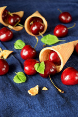 Waffle cones and cherries on blue background. Ingredients for a dessert cooking