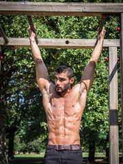 Attractive man exercising and working out in outdoor gym in city park