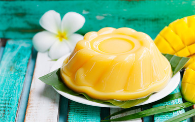 Mango pudding, jelly on white plate with palm leaf