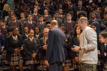 Britain's Prince William and rapper Professor Green surprise children taking part in an assembly on cyberbullying and its effect on young people's mental health during an unannounced visit to Burlington Academy, London
