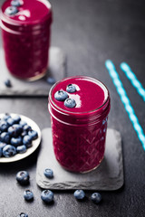 Berry smoothie with fresh blueberries on a black stone background