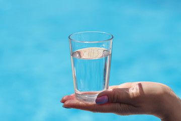 A glass of water in hands on blue background
