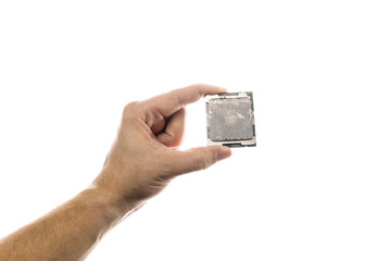 CPU with old thermal paste on IHS in man's hand isolated on white background.