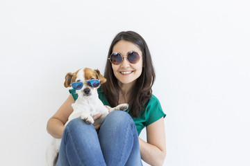 Beautiful young woman playing with her little cute dog at home. Lifestyle portrait. Love for animals concept. white background. Both wearing sunglasses