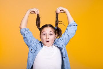 Cute teenage girl rising her hairs up in the studio on yellow background