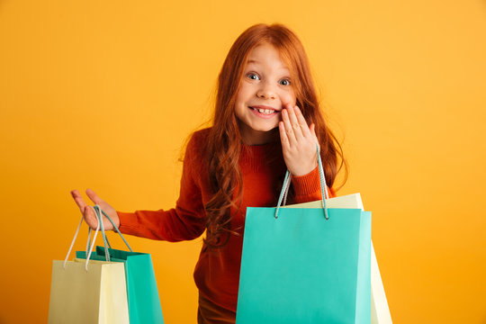 Happy little redhead girl holding shopping bags. Looking camera.