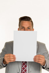 manager holds blank sheet in front of face