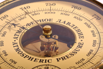 Old yellow-brown aneroid barometer in wooden body close-up