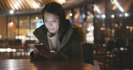 Woman using mobile phone outside restaurant at night