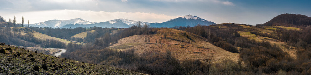 panorama of Borzhava mountain ridge in springtime. beautiful countryside with snowy tops and forested hills. location Volovets, Ukraine