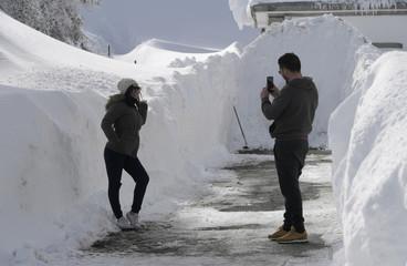 A couple takes photos at the mountain pass of Pajares