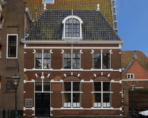 A traditional old dutch house with windows a door and roof tiles front view at the Pieterskerkhof in Leiden