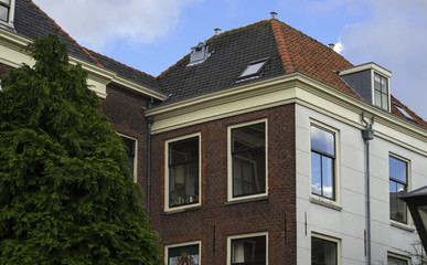 Leiden, THe Netherlands - January 20th 2018 - A traditional old dutch house with a orange rooftop and a green tree infront of the house