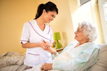Beautiful nurse holding hand of old senior patient and comfort her