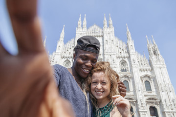 Young couple in love taking a selfie in front of the Milan Cathedral in summer, Italy