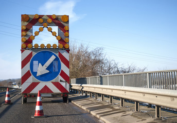 Baustelle auf einer Brücke mit Baustellenfahrzeug und Warnschild, Fahrbahnverengung
