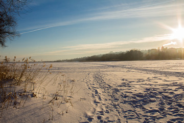 A beautiful winter landscape, a sunset and an unusual sky, against the background of snow and the trail leaving in the distance