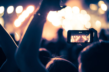 abstract colorful background of hand holding smart phone to taking memories by capture image photo and record video of lighting and people crowded in concert music event.