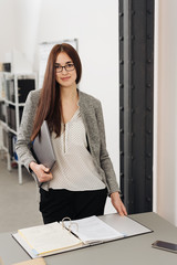 Young woman standing over binder in office