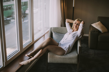 Blond woman sitting by window at day light