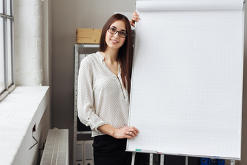 Young smiling woman standing by blank flip chart