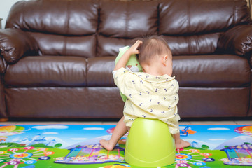 Cute little Asian 18 months old / 1 year old toddler baby boy child scratching head sitting on potty playing with stuffed animal toys in living room at home in morning time, Toilet training concept