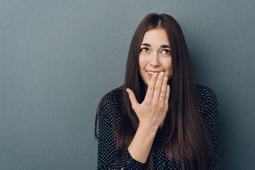 Embarrassed or polite young woman hiding her smile