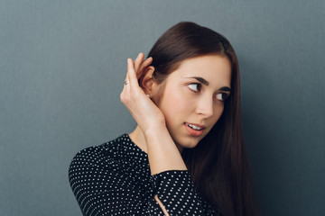 Young woman making a hearing gesture