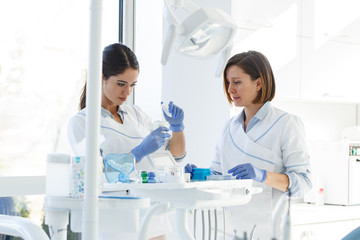 Female dentists in dental office .They cleans  equipment for next working day.