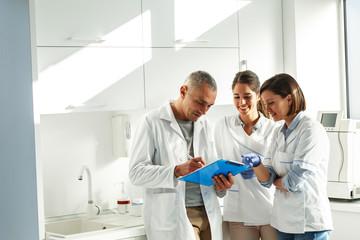 Medical dentist team in dental office   examining list of patients.