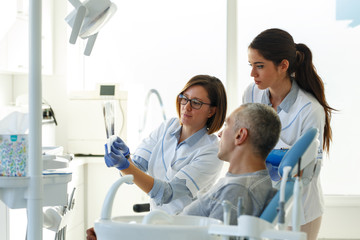 Dentist and her assistant in dental office talking with male patient and preparing for treatment.Examining x-ray image.