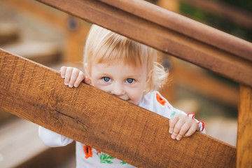 1 year old little caucasian girl palaing hide and seek game outdoors on sunny warm summer day. Closeup portrait of tricky face of blonde baby hiding from parents. Horizontal color photography.