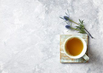 Cup of Tea and Sea Holly Flowers on gray stone background