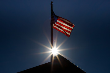 American Flag In Front of A Sun Flare