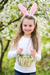 Girl smiling in bunny ears with basket