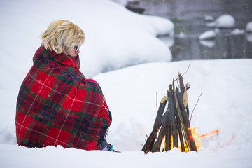 The girl sits at the fire in winter in the woods