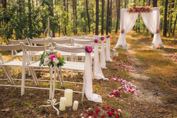 Beautiful elegant wedding decorations of place for ceremony outside in old wood with huge pines trees. Horizontal color image.