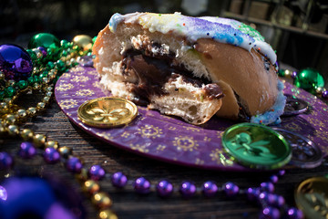 king cake slice with chocolate pudding filling surrounded by mardi gras decorations