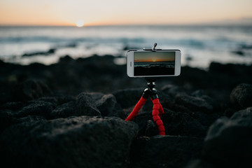 Mobile phone on the tripod shooting the sunset on the rocky shore of the ocean
