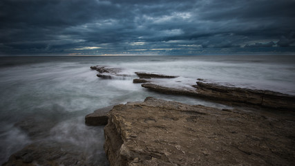 Beautiful rocky beach in the Portuguese coastline in a stormy day. Seascape. Long exposure