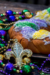 king cake surrounded by mardi gras decorations