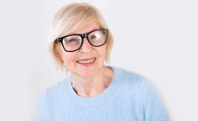Portrait of a smiling old woman wearing glasses. Beautiful modern grandmother is 70 years old - a pensioner.