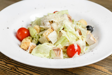 Chicken caesar salad with lettuce leaves in white bowl on wooden table